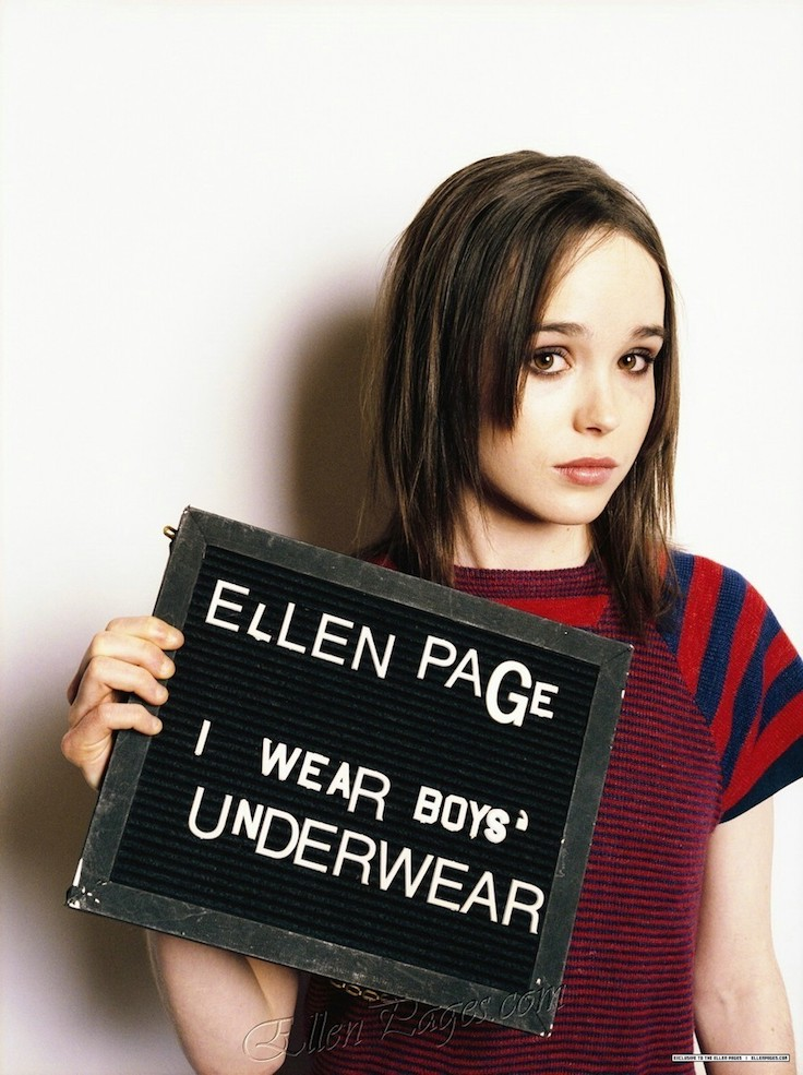 """I have no idea what the context for this photoshoot was, but it seems relevant.   Image description: Ellen Page, a woman with light skin and shoulder-length straight brown hair, holds a sign that says """"ELLEN PAGE I WEAR BOYS' UNDERWEAR."""" She is standing against a white wall, looking at the camera, and wearing a striped red and blue shirt."""