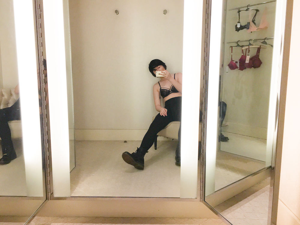 So much beige.   Image description: A Chinese-American woman wearing a black strappy bra, black high-waisted pants, and black Dr. Martens combat boots takes a mirror selfie in a fitting room. She is sprawled out on a beige chair next to some bras hanging on a rod on the wall.