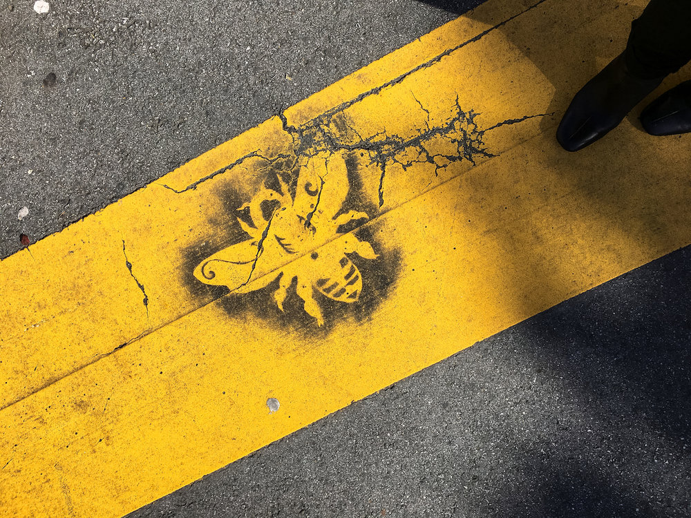 image description: A stencil of a honey bee applied with black spray paint to a yellow street crossing. A person's black boots are visible in the upper right corner of the photo.