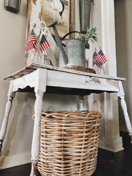 Patriotic decor on foyer table with flags.