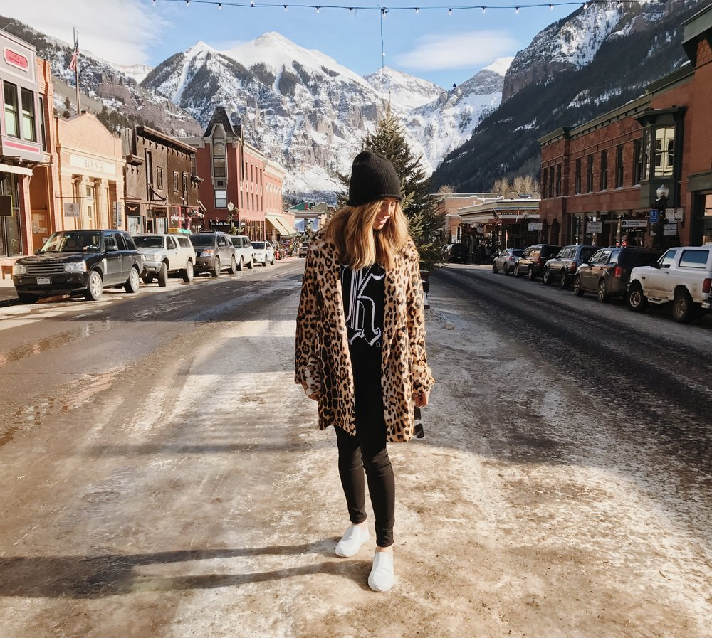 Kelley Fertitta bundled up in a beanie and leopard print over coat in Telluride, Colorado