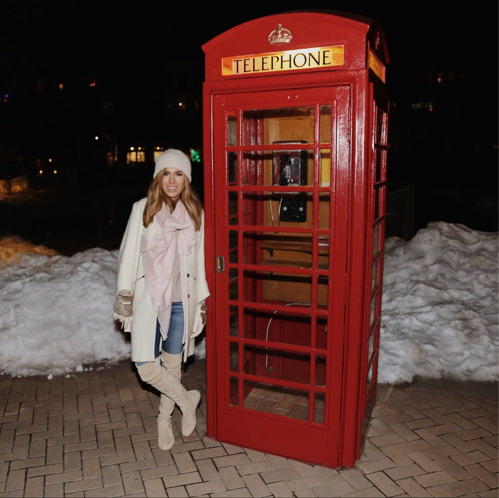Kelley bundled up standing next to antique phone booth in Telluride
