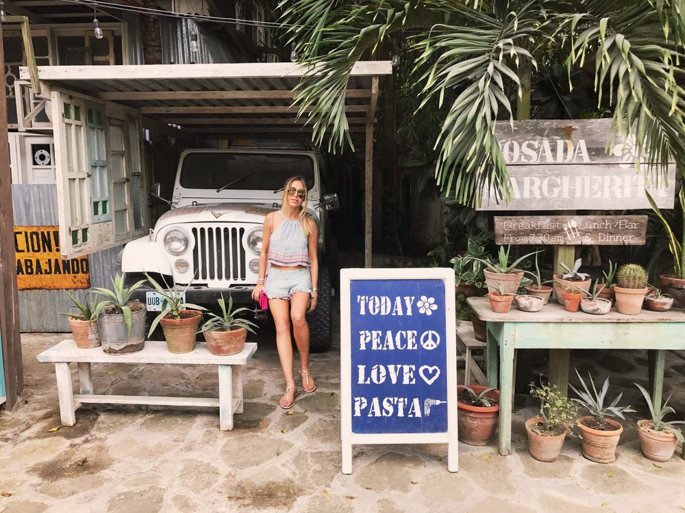 Wilson hanging out in front of a vintage Jeep in Tulum Mexico
