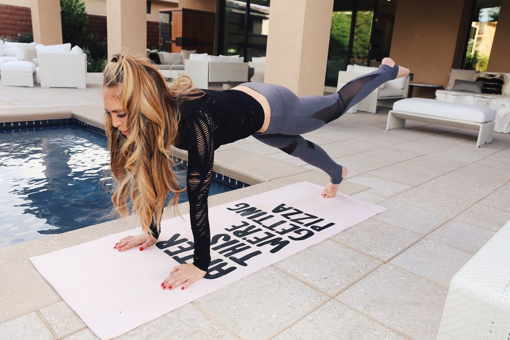 "Kelley Ann Fertitta doing yoga on a mat that says ""After this we're getting pizza!"""