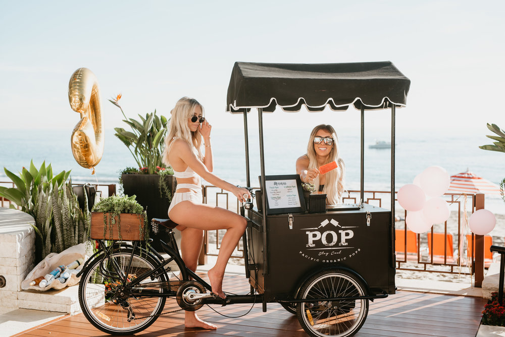 Kelley & Victoria  Fertitta posing with organic pop cart on Laguna Beach