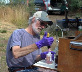 Larry Marxer measuring dissolved oxygen in river water, using the Winkler method.