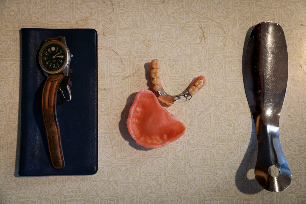 My grandpa's belongings lying on the coffee-stained countertop: his daily-worn watch, pocketbook, teeth and shoehorn.  This is an image from an on-going personal project.