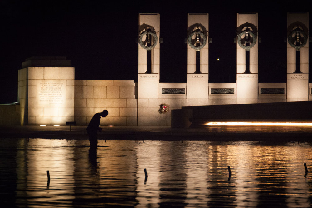 A man wades through the waters of the World War II memorial waters at night in search of change in Washington D.C.  This image was made for the Associated Collegiate Press Shoot-Out in October 2016.