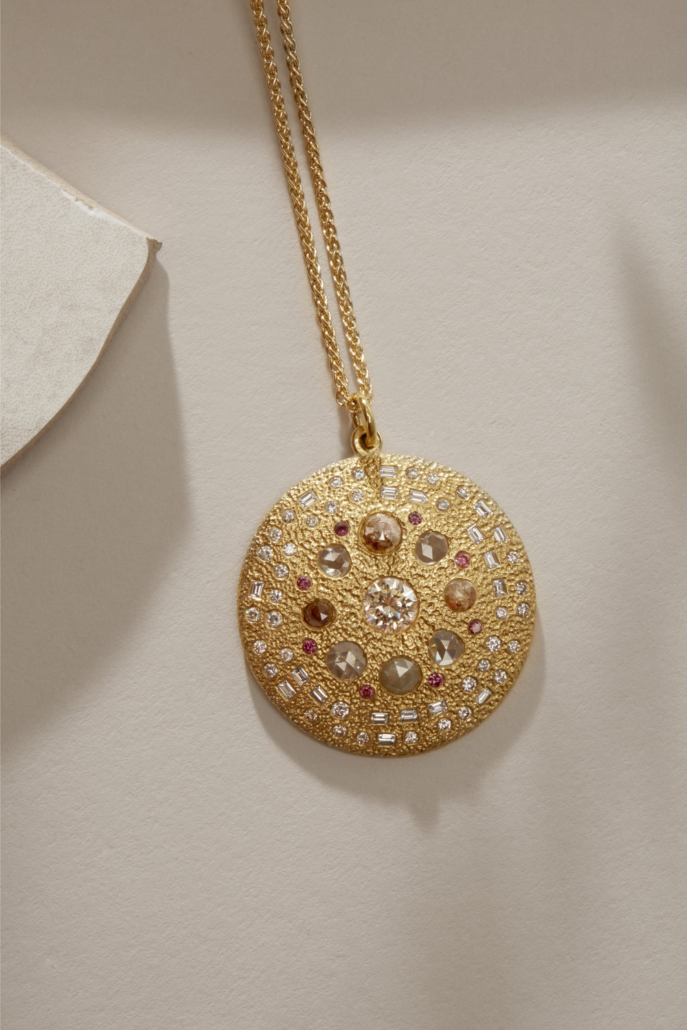 A bespoke pendant using Morse Code round and baguette diamonds to hide the family's names from £10,000