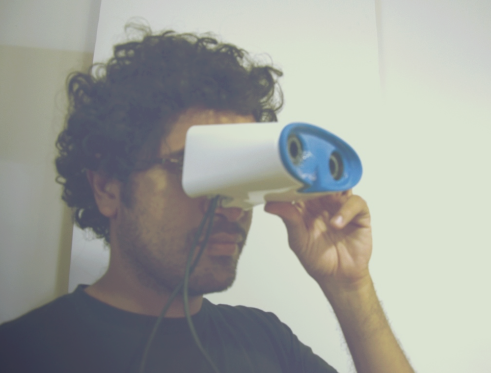 Saurabh Bhide tests the prototype. The white shell is attached with a smartphone that displays a test image. It's further connected to a camera to detect the eye motion to understand the deviation of the pupil from the median.