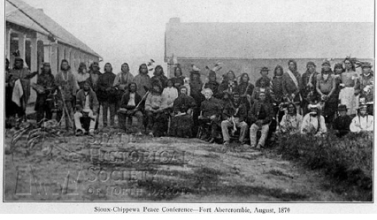 "Sioux Chippewa Peace Treaty Aug., 15 1897 - ""In late April 1869 the Ojibway chief Niigaaniibinesi, or Flat Mouth II, of Leech Lake, killed one of the former scout leaders, Wasuideya [Sets Fire to Hail], near Toqua Lakes (in Big Stone County, Minnesota). Wasuideya´s wife, Icagowin (Makes Her Mark Woman), who was Gabriel´s [Renville] aunt, was taken captive. […]As Little Paul [Paul Mazakutemani, Wahpeton chief] and all of the Sisseton and Wahpeton leaders had renounced warfare with their fellow Indians years before, they stood ready to promote peace. They had such an opportunity during the summer of 1870 when they were contacted by Waabiaanakwad (White Cloud), the leading Ojibway chief at the White Earth Reservation in Minnesota. […]Messengers were sent to the Sisseton and Wahpeton leaders, asking them to meet an Ojibway delegation at Fort Abercrombie, that Waabiaanakwad was offering to give the murderer´s annuities to the relatives of Wasuideya. Father Genin volunteered to act as a mediator.Little Paul, along with chiefs Wasuiciyapi [Hail that Strikes Itself aka Sweet Corn, Sisseton], Hupacokamaza [Iron on the Inside of his Wings aka Metal Wing, Sisseton], Wasukiye [Causes Hail, Sisseton], and Wanbdiupiduta [Scarlet Plume, Sisseton] arrived at the fort on August 12. […] The following day the Ojibway arrived, among them chiefs Waabiaanakwad [White Cloud], Mezhucegiihig (Horizon), and Manidoowaabi (Spirit Vision). […]The next day, August 15, the Indians attended a mass given by Genin and then went into the fort to sign a treaty of peace. It stated that the two parties wished to make an ""everlasting peace"" and to ask government authorities to punish any offenders. A peace dance was celebrated throughout the day inside the post. At the end a photographer (Landgeving) took a photo of the group. Genin was in the center, with Wasuiciyapi to his right. Little Paul is seated third to the right of Genin.""Mark Diedrich: Little Paul – Christian Leader of the Dakota Peace Party, Coyote Books 2010, page 172/173"