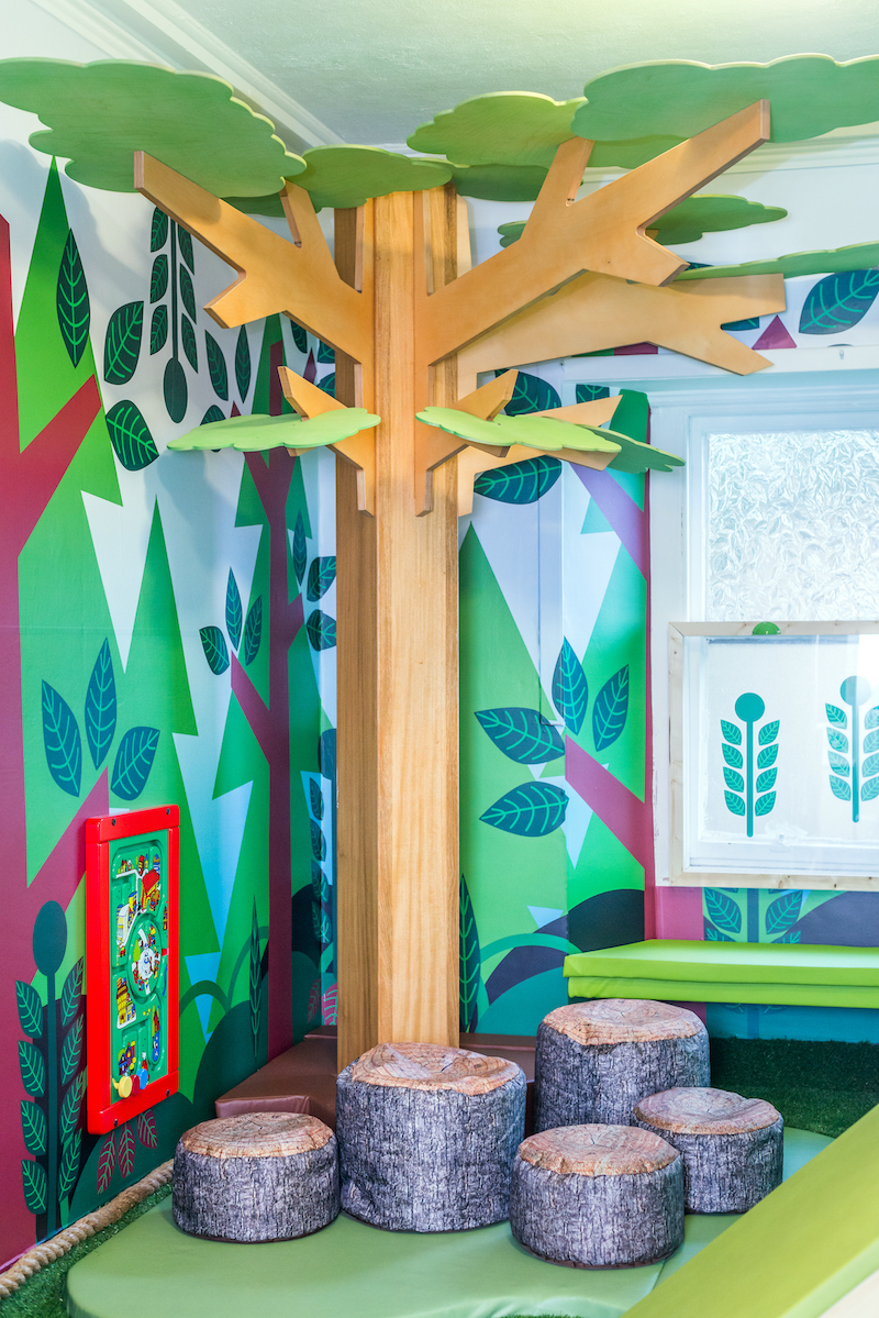 The woodland theme is accentuated with a life size tree, log seats and wall decor, providing an immersive experience.
