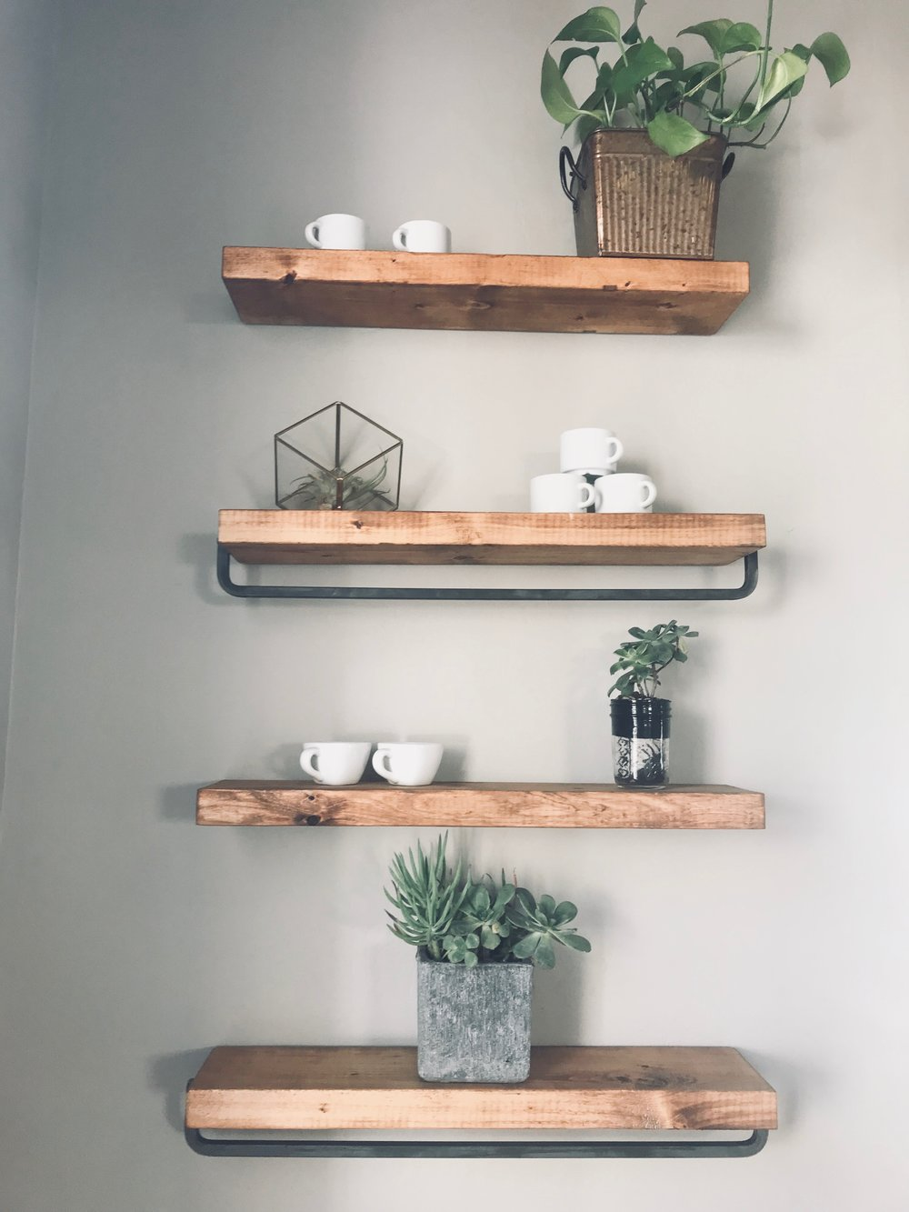 Reclaimed wood floating shelves with metal bars are perfect for displaying coffee for sale and this by far is my favorite wall treatment in the space.