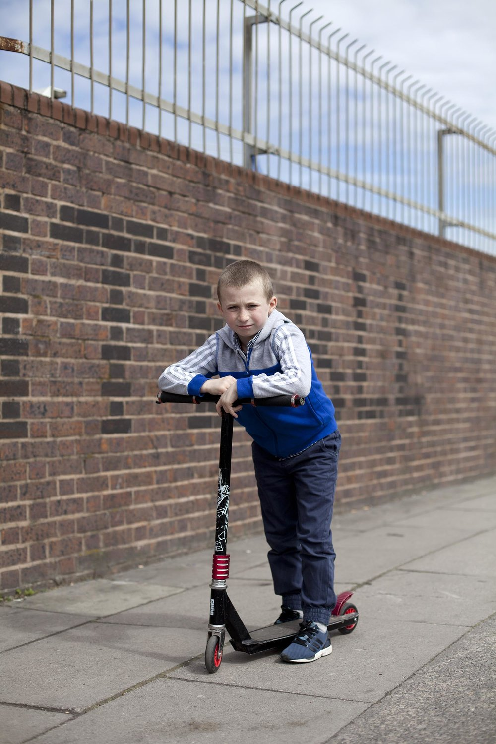 Boy rides scooter outside Everton's ground Goodison Park, Liverpool     Goodison to Anfield with 11 Freunde     A documentary photography collaboration with Ron Ulrich from the German football magazine 11Freunde. Our brief was to walk from Goodison Park to Anfield collecting photographs and stories that told of the area, its people and the changes to both as money flowed into football, but didn't necessarily find its way into Liverpool. In a day of scouse Gonzo, we allowed the story to pull us along, to church, Susan's Salon, several boozers and Stanley Park, the grandiose Victorian centre ground.  Beautifully designed and researched, 11 Freunde has the grass roots of football at its heart so a feature on the people and places surrounding the Liverpool giants seen in it's pages seems apt.   In June, on the days surrounding the Champions League final in Berlin, the spreads were used to advertise the magazine across the city, proudly placing the gritty, boarded-up realities of traditional football into the monied glamour of Europe's most glittering prize.