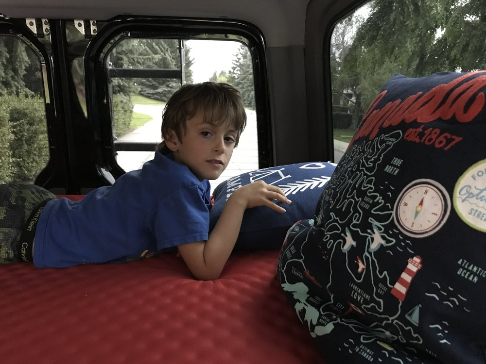 Ben vegging in the bed at the back end of the van.