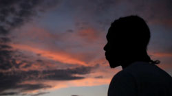 a teenager's silhoutte against the sunset