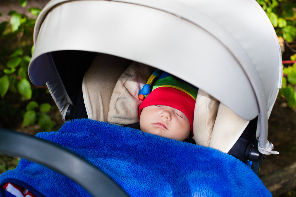 newborn baby with rainbow hat and blue blanket in a car seat.