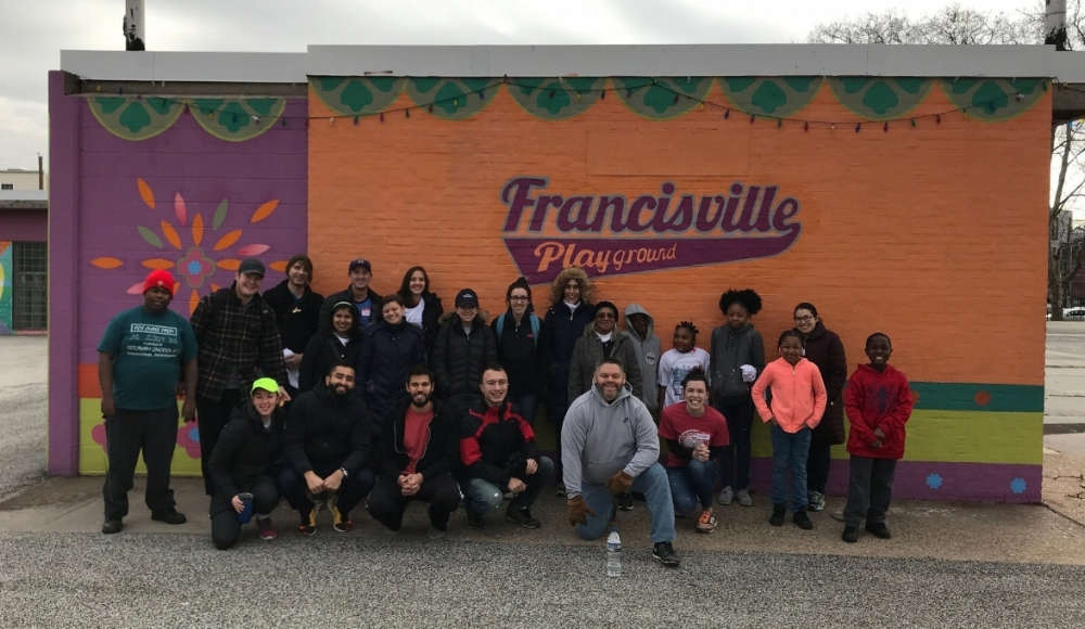Volunteer group in front of Francisville Playground sign
