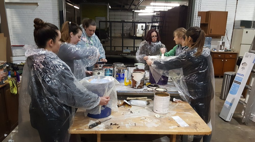 Volunteers combining paint into full cans for sale at Philadelphia Community Corps!