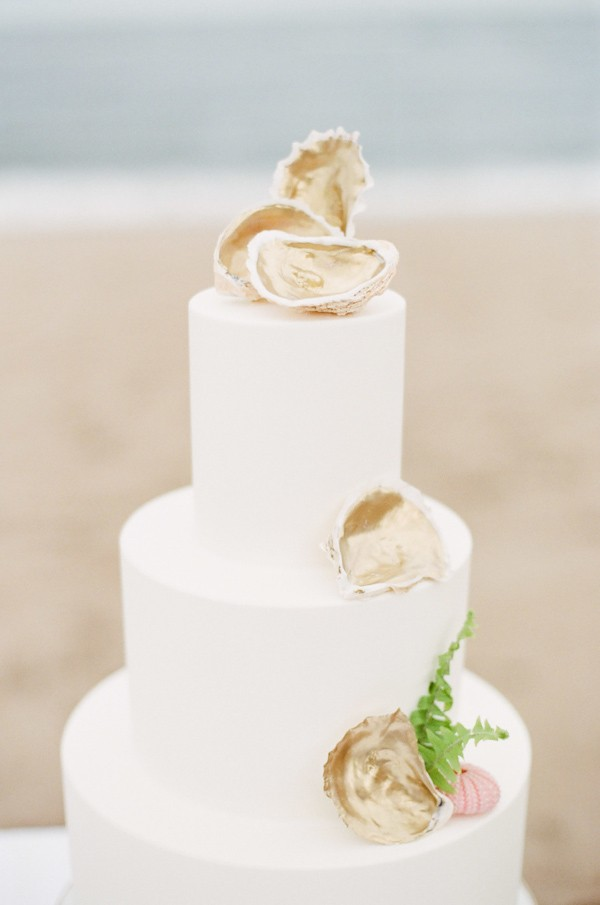 Beach wedding cakes trendy bride fine art wedding blog planning the bottom layer has a small pink anemone with a touch of fondant seaweed while the cake is topped with a collection of shells to tie the look together junglespirit Image collections