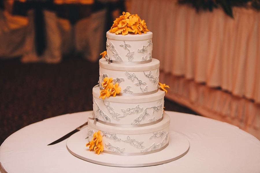 white and gray wedding cake with yellow accents