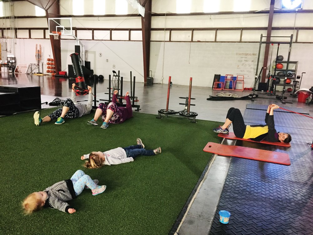 Moms work on their core strength as the littles perfect their glute bridges.