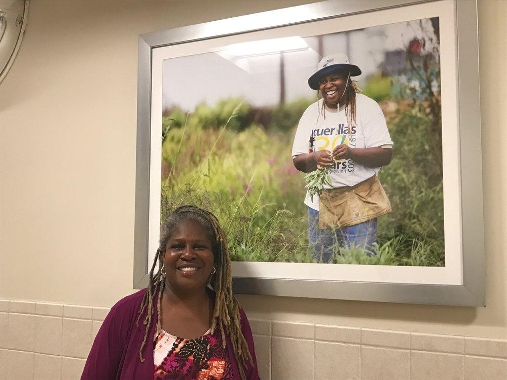 Activist Karen Washington standing with exhibition image in ARTViews Gallery.