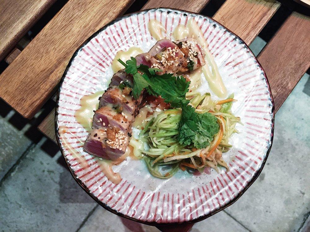 Yoyoki tuna tataki with garlic sauce, namtuk sauce, and mango salad on the side.