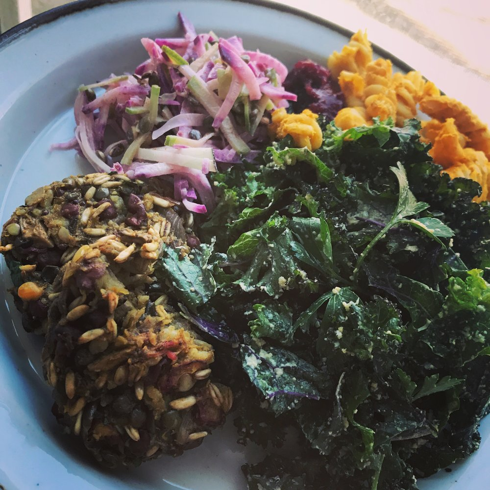 "A leftover feast! sprouted legume patty, kale salad with whole orange dressing, ""umami mac"", cranberry sauce, and radish slaw."