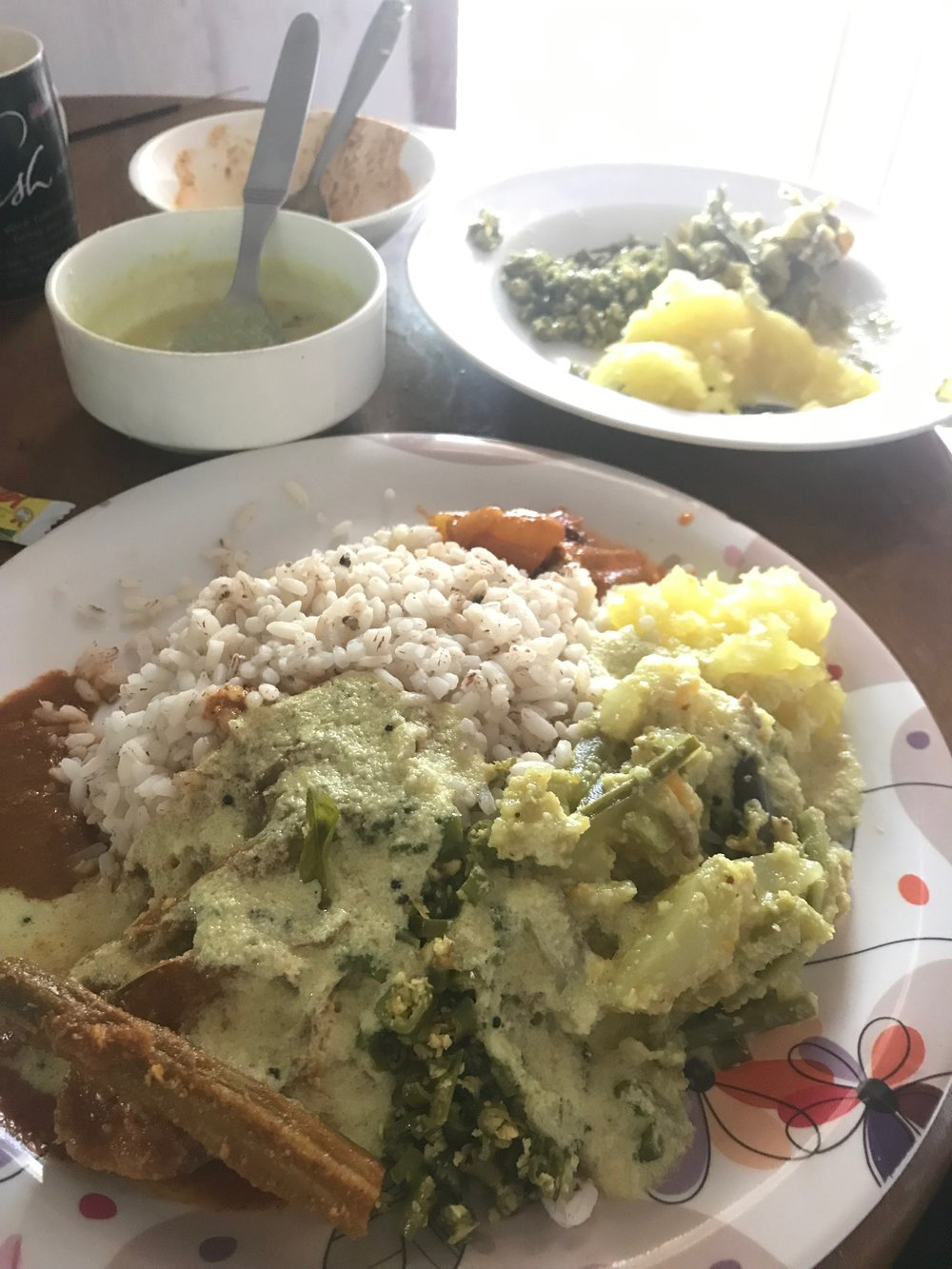 "Local rice, cassava smash, aviil, fish curry featuring a delicious ""drumstick"" (local vegetable), green onion thoran, doused in coconut curry sauce."