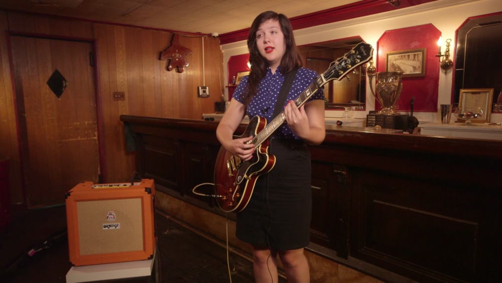 Lucy Dacus plays guitar and sings in front of a dimly lit basement bar.