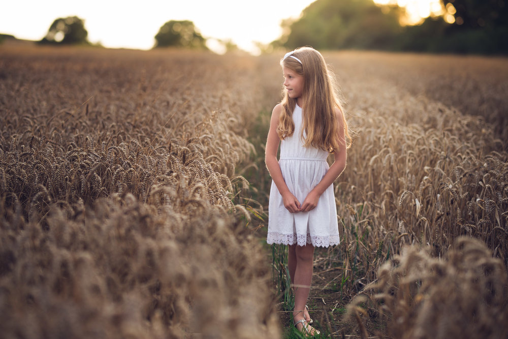 Girl in wheat field looking away | Children's Photography