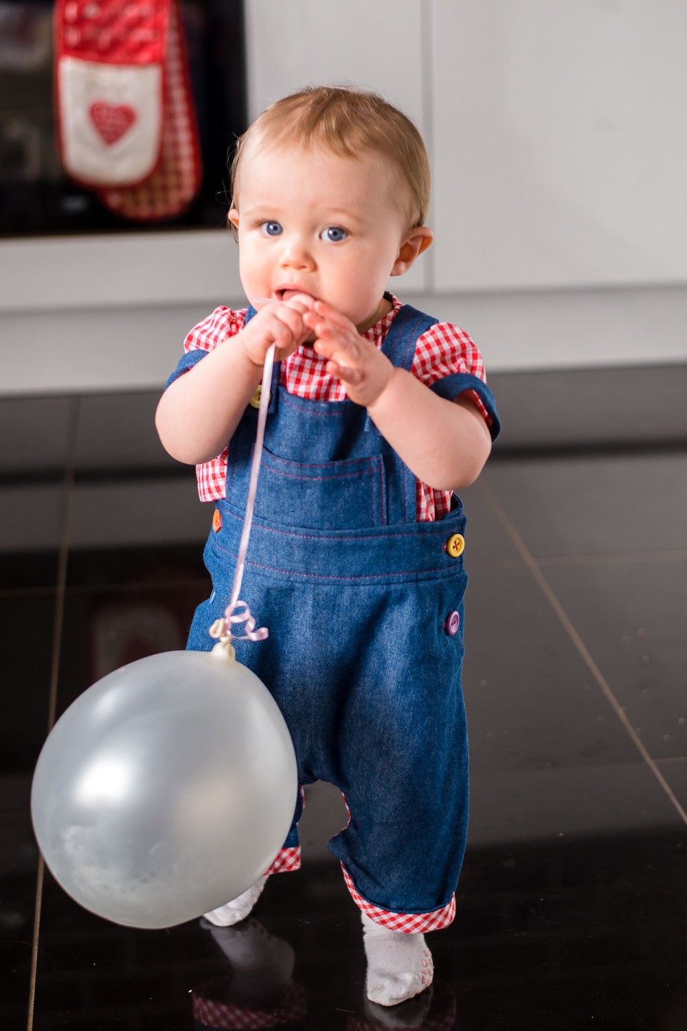 Balloon and dungarees in kitchen | Children's Photography