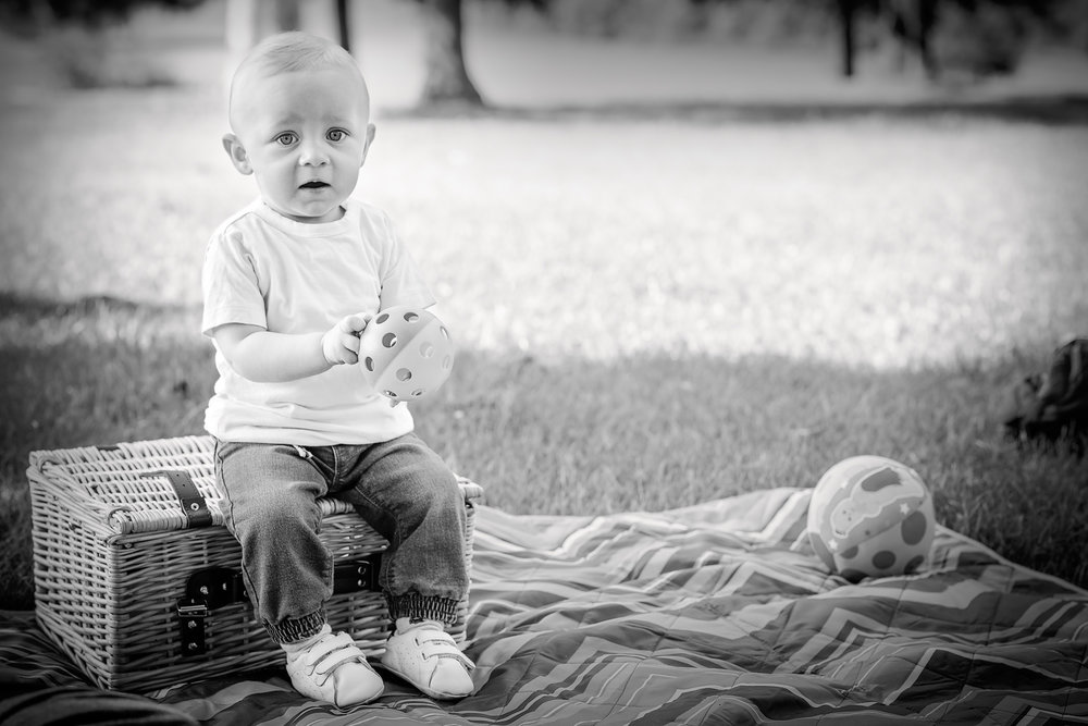 Baby boy on picnic basket holding toy | Children's Photography
