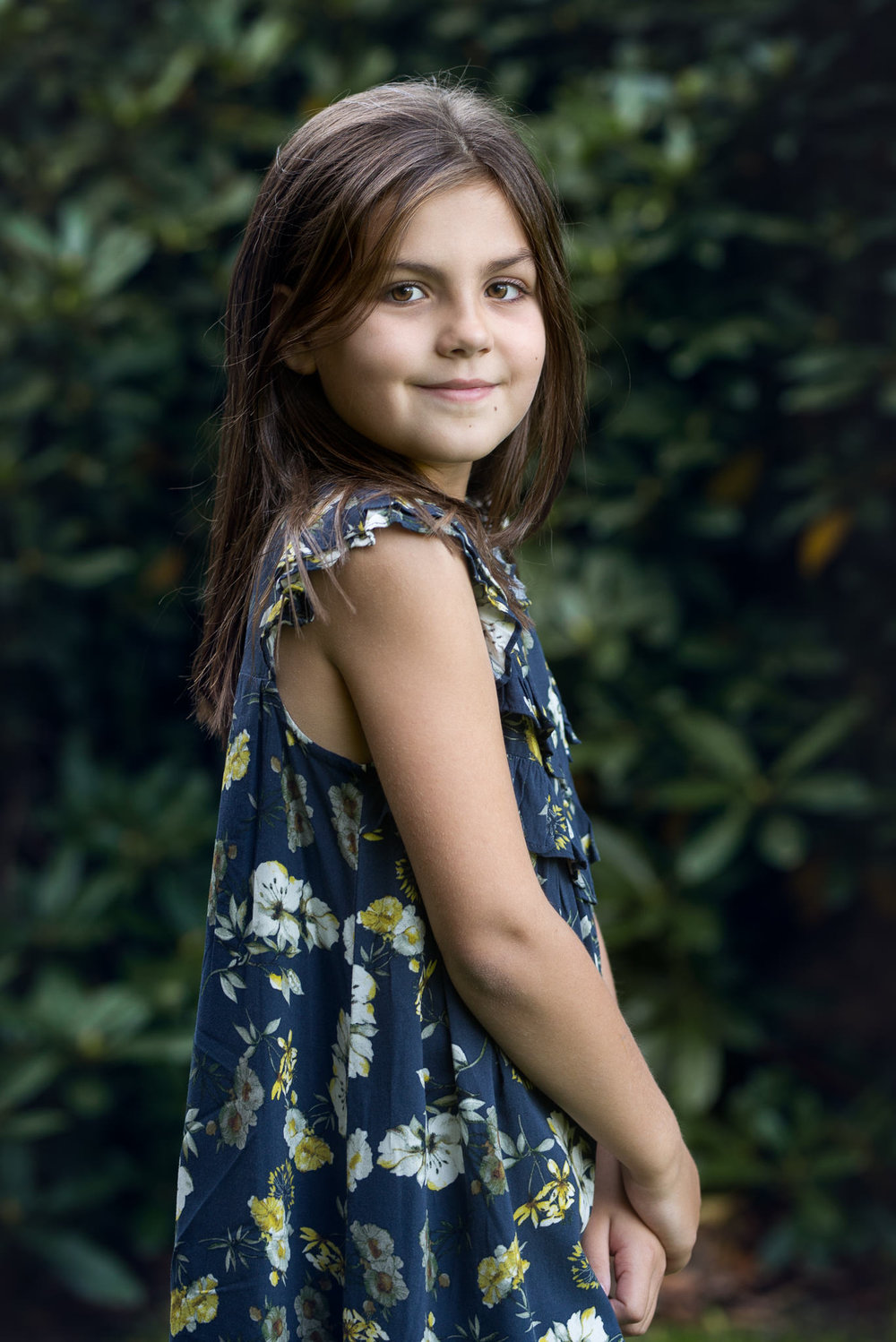 Girl stood against greenery | Children's Photography