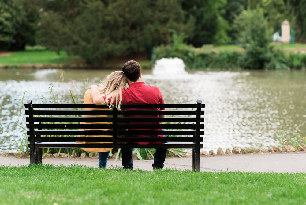 Couple cuddling on a bench at Pittville Park - Cotswolds Wedding Photographer