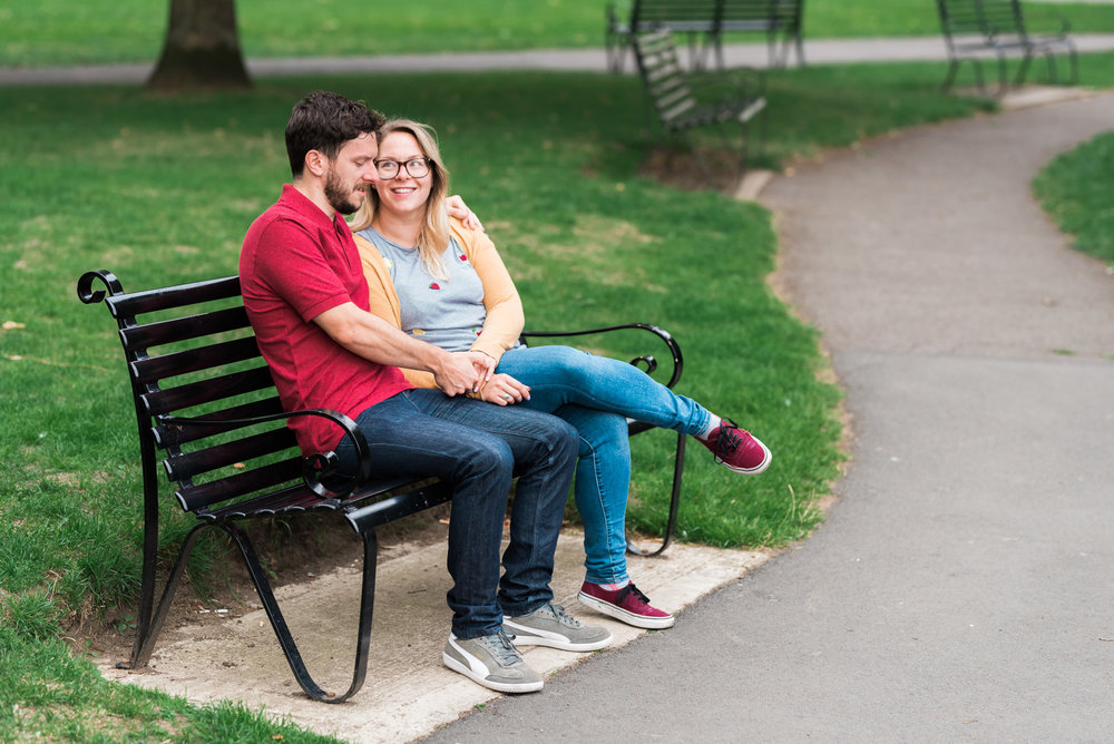 Engaged couple laughing on a bench - Cotswolds Wedding Photographer