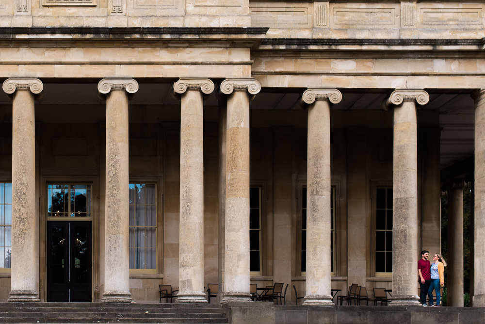 Couple stood against a pillar at Pittville Pump Rooms - Cotswolds Wedding Photographer
