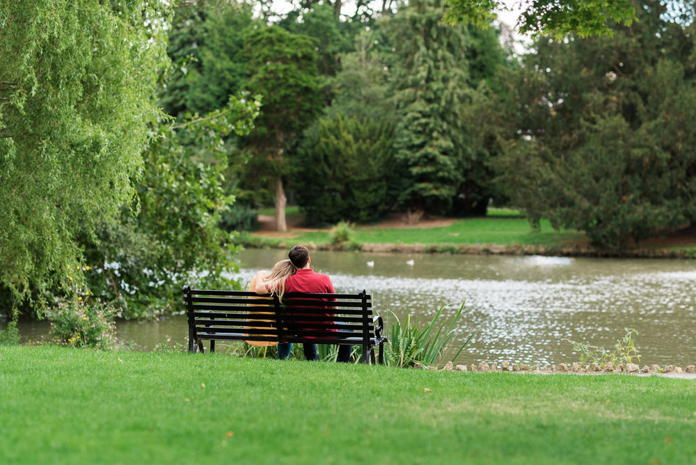 Couple cuddling up on a bench at Pittville Park - Cotswolds Wedding Photographer
