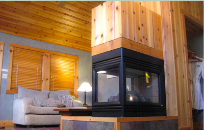 Flatscreen TV swivels above fireplace for viewing from living area, bedroom or the whirlpool.