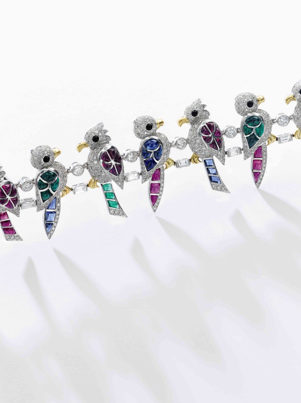 Gem set and diamond bracelet, 'Perroquet' - designed as a line of parrots, their wings and tails set with cabochon sapphires, rubies and emeralds