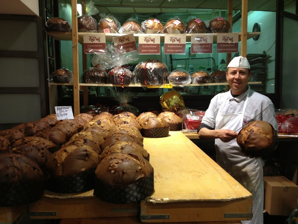A baker at Roscioli taking freshly-baked panettoni out of the oven to cool. © Tiffany Parks
