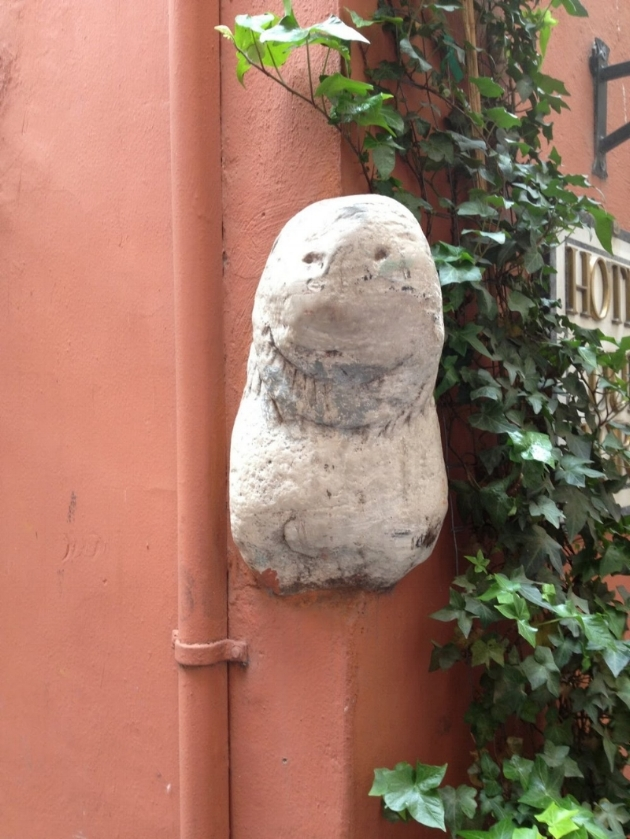 Small statue of a lion's head embedded into the side of a building on Via del Leonetto