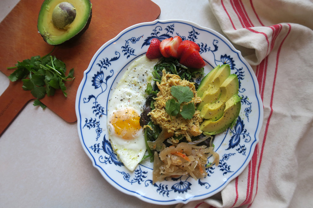 Shredded chicken on wilted greens with avocado, cilantro, an egg, and kimchi!  Made a great breakfast salad.
