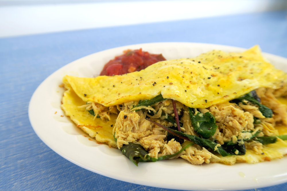 A two egg omelette with shredded chicken and greens.  Salsa on the side.  Yum.