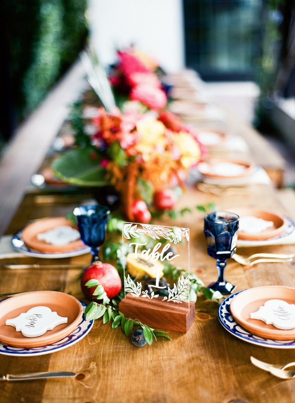 Sage Bleu Catering outdoor table setting with pottery plates and beautiful florals.