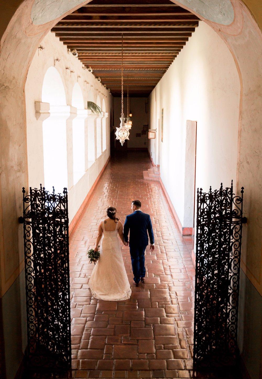 Newlyweds walking down tiled mezzanine