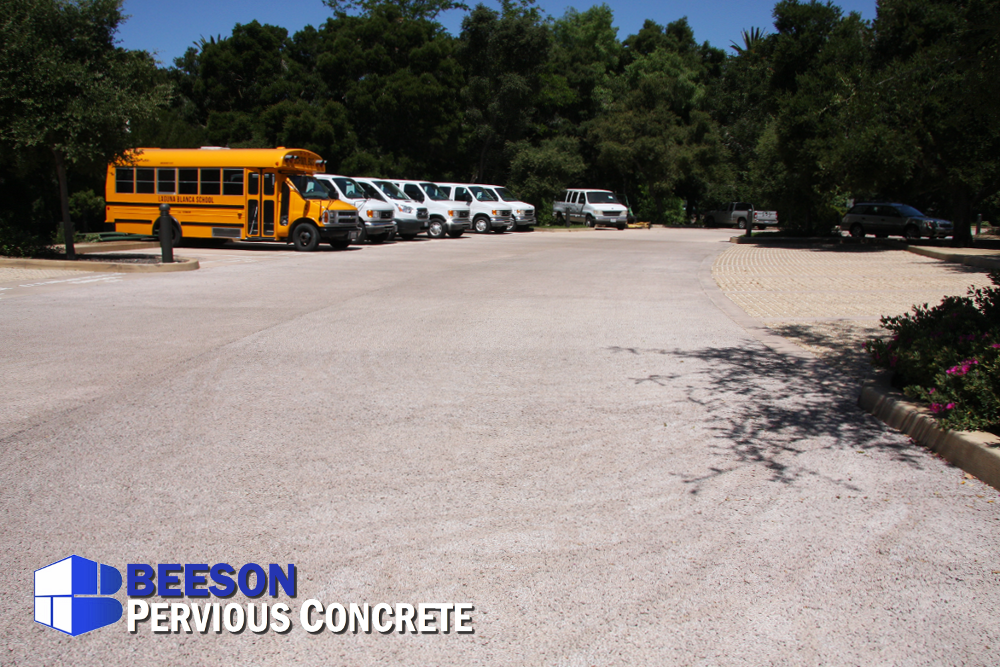 Pervious concrete sweeps around as the drive isle with porous pavers filled with gravel are the parking stalls.