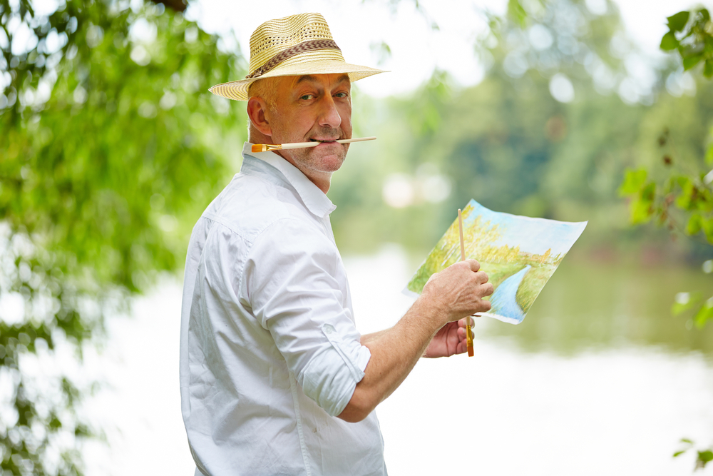 Older white man wearing a sun hat, holding a paint brush in his mouth and  a water color painting in his hand.