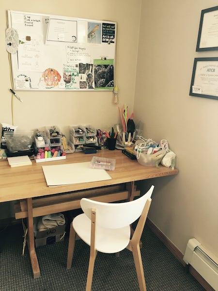 Valerie's art making desk with whiteboard above.